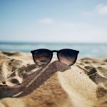 Summer job search. Image of a pair of sunglasses sitting on the sand on a beach with a blue slightly cloudy sky.