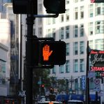 Slow your job search. Photo of a crosswalk sign indicating to stop in a busy city.