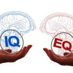 emotional intelligence. one hand holding a brain with the letters IQ and another hand holding brain with letters EQ