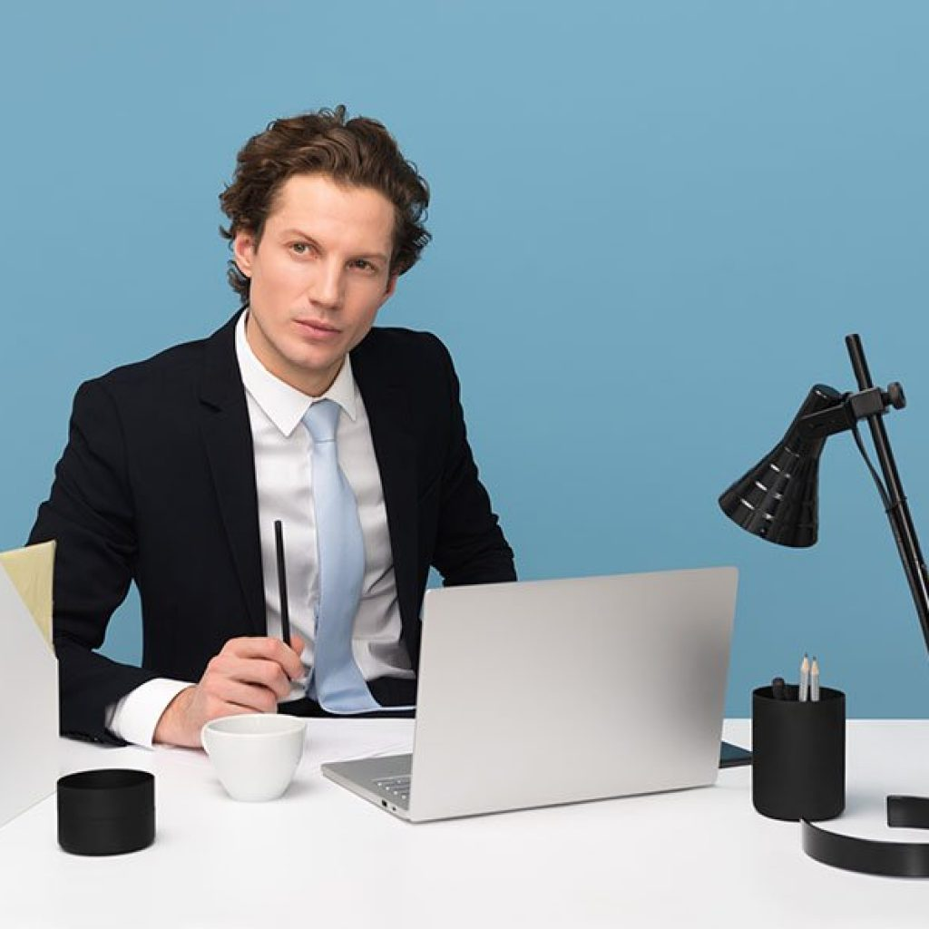 what is your dream job: an image of a young man in a business suit looking upward thoughtfully at a clean white desk with a potted plant.