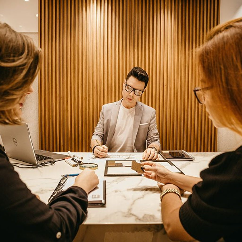 Where does your boss think you are? a person in an interview looking down and checking their notes, while two interviewers in the foreground look at him.