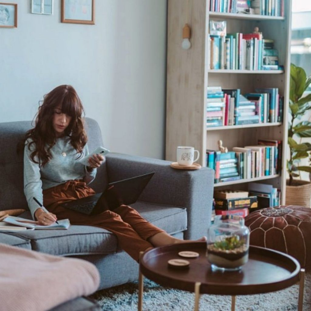 post-pandemic world. Young woman sitting on a couch in an apartment working on a laptop